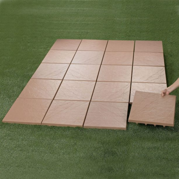 installing interlocking patio tiles on a flat-surface grass