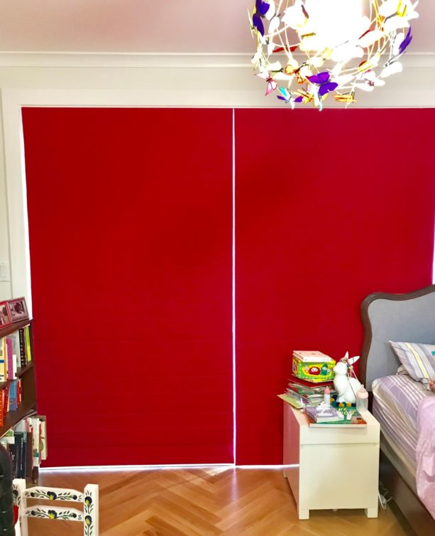 solid crimson red flat roman shade in a modern bedroom