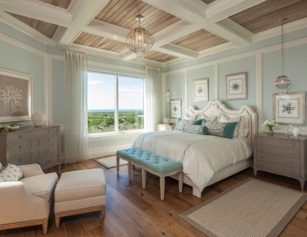 a beach-style bedroom with white trim, soft blue walls, and white oak floor