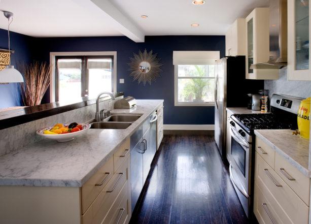 a contemporary kitchen with dark wood floor, white trim, and dark blue walls