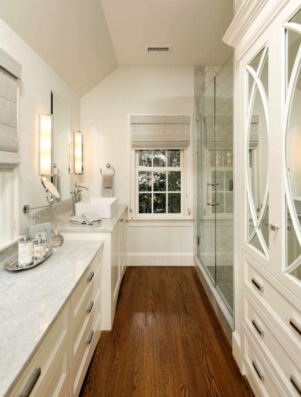 a narrow traditional bathroom with white trim and dark wood floor