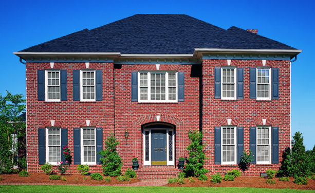 a traditional red brick house with deep blue shutters
