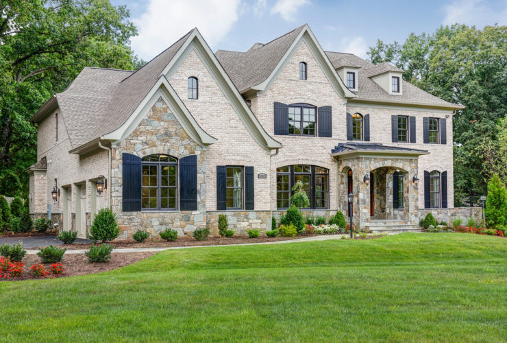 a traditional tan brick house with navy blue shutters