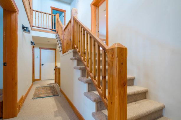 an interior with white doors, stained wood trim, and stair railing with coordinating look