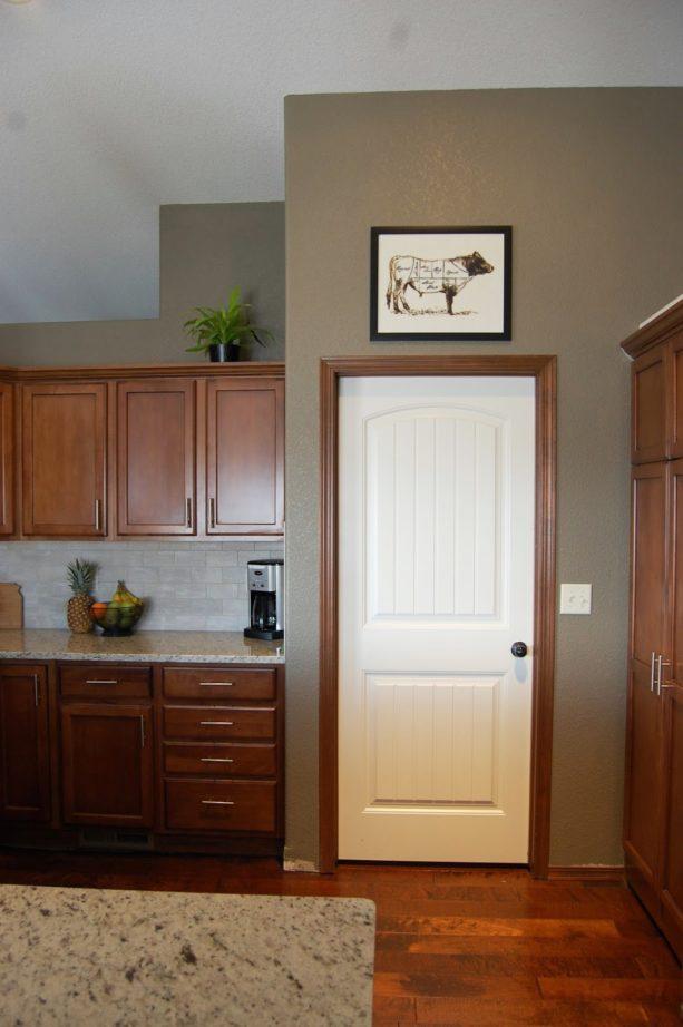 the combination of white door, dark wood trim, and dark wood kitchen furniture