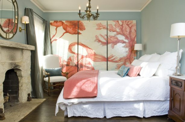 a Mediterranean bedroom with blue domination and an enormous coral color artwork as the focal point