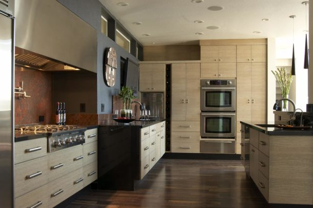 a contemporary kitchen with rift sawn white oak cabinets, stainless steel appliances, and dark grey wall paint