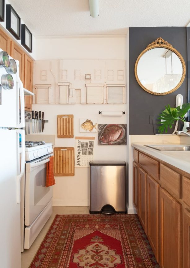 a small kitchen with creamy white wall paint, honey oak cabinets, and white appliances