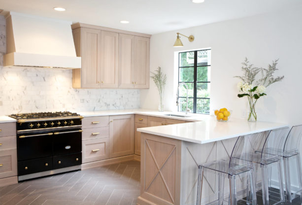 a transitional kitchen with quarter sawn light oak cabinets, light grey wall paint, and black stove