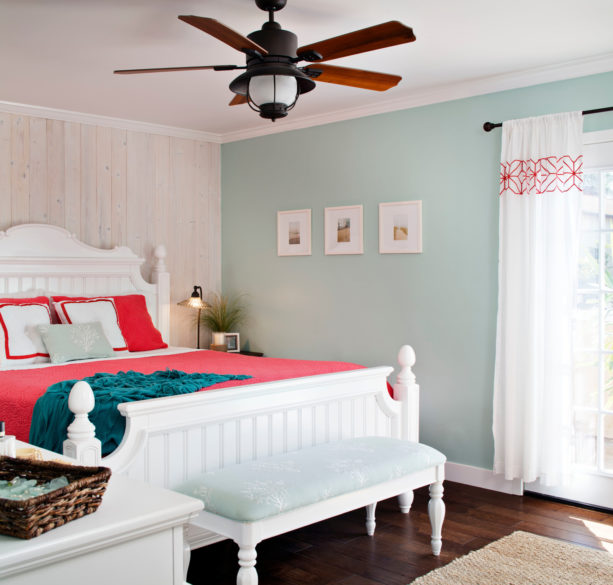 a white bed with coral bedding and ocean blue blanket