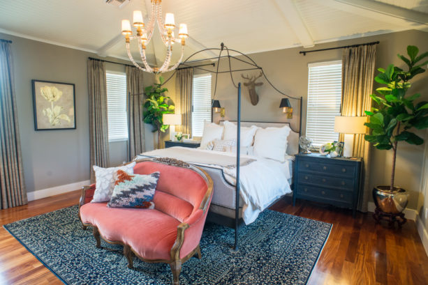 adding a coral tone by placing a sofa in a dark blue and grey bedroom
