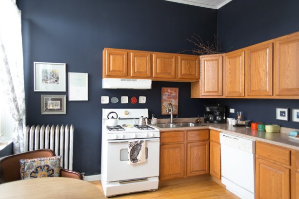 honey oak cabinets paired with dark blue wall paint and white appliances