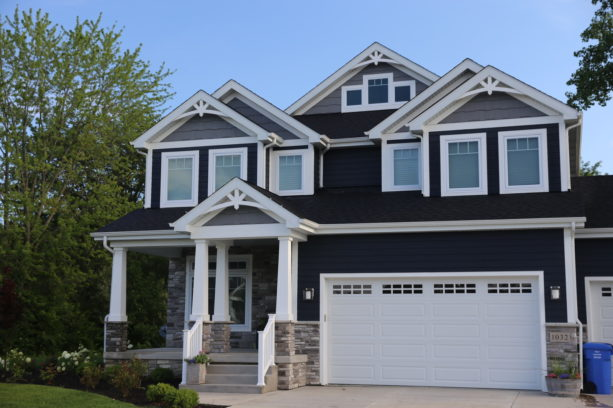 a dark navy craftsman house with white trim