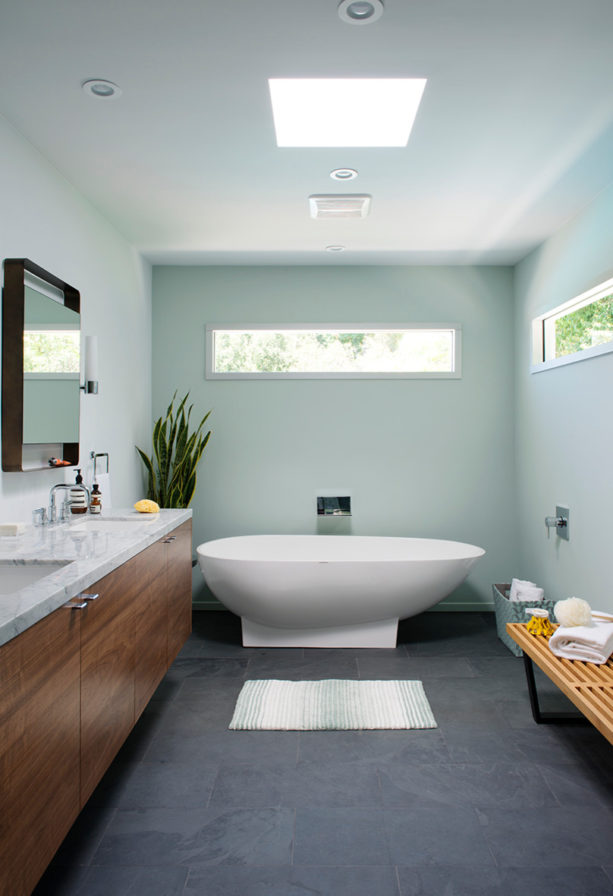 a mid-century modern bathroom with grey slate floor