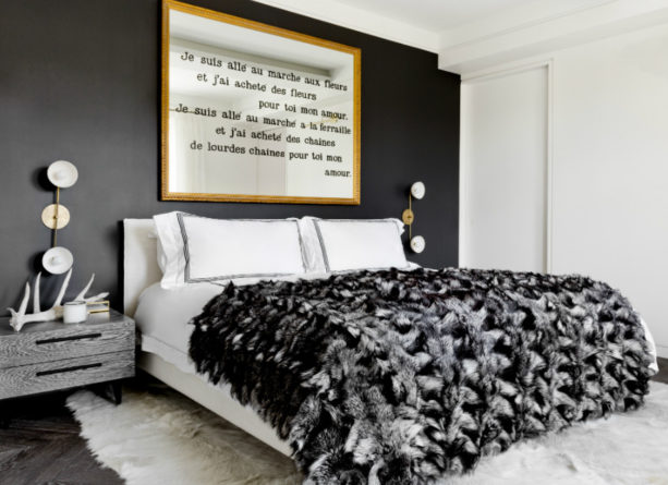 a modern bedroom with black accent wall and gold-framed wall art
