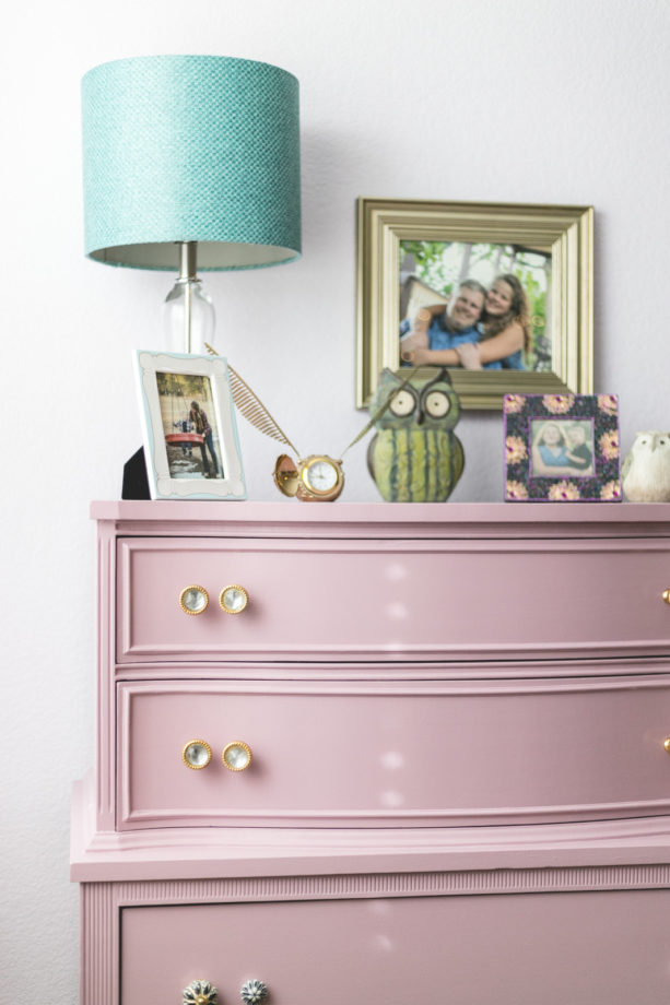 the pink dresser in the corner of the pink and mauve shabby chic bedroom