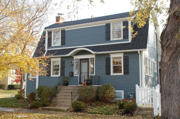 traditional blue house with white trim and black shutters