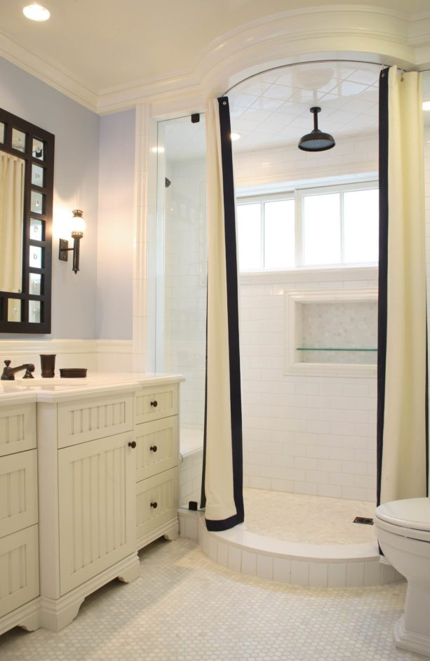 a shower room with white subway tile and snow white grout