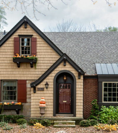 a traditional exterior with tan wall siding and red wood shutters
