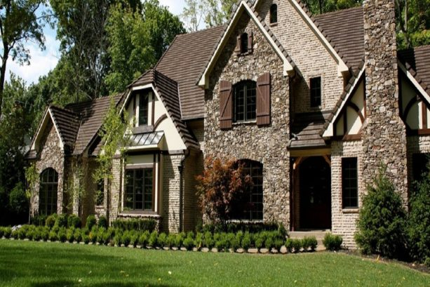 a traditional exterior with the mixture of brown roof, cream stucco, stone wall, and brick wall