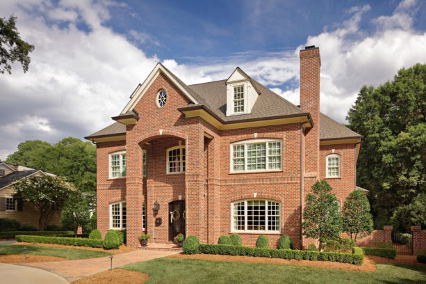 a traditional red brick house with medium brown roof