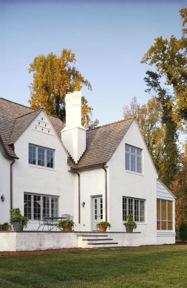 an antique white traditional exterior with medium tone brown roof