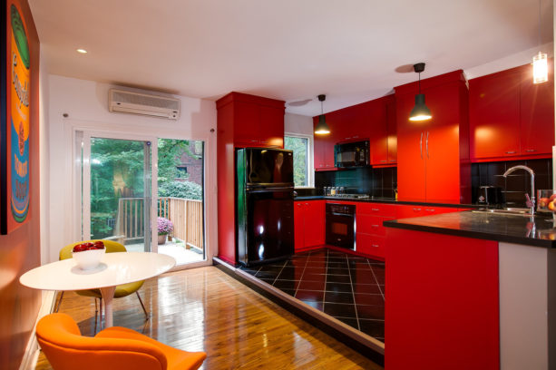 a contemporary red kitchen with black appliances