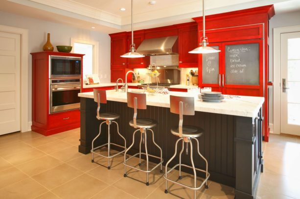 a set of red custom cabinets paired with black island in an eclectic kitchen
