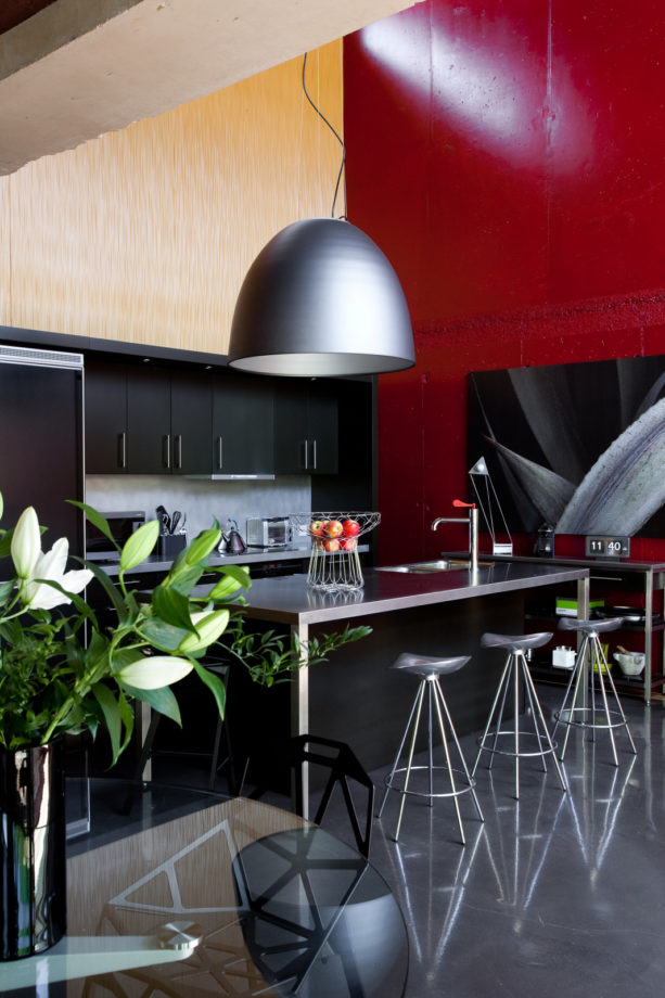 a stunning red accent wall in a black contemporary kitchen