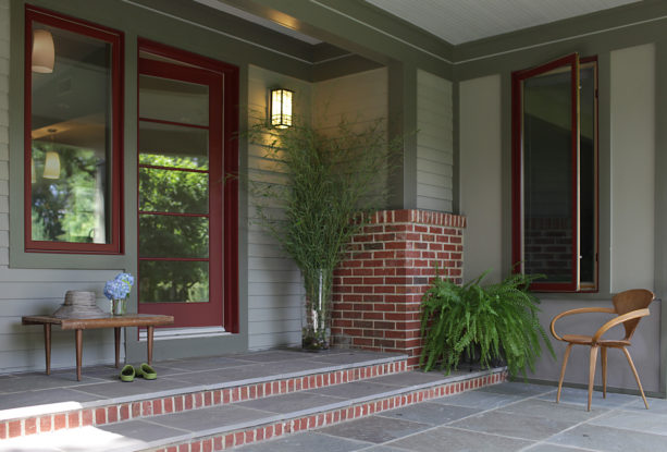 a traditional entry with sage green siding and red brick detailing
