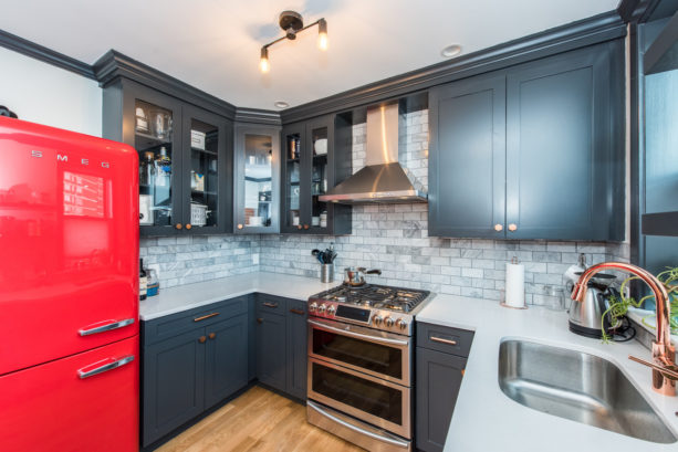 a transitional kitchen decorated with black cabinets and red retro fridge