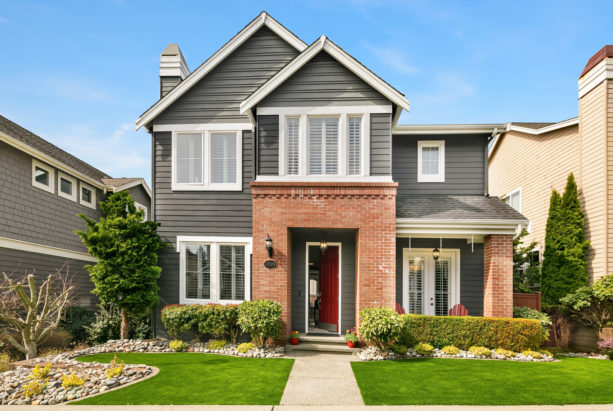 a trendy transitional house with grey siding and red brick combo