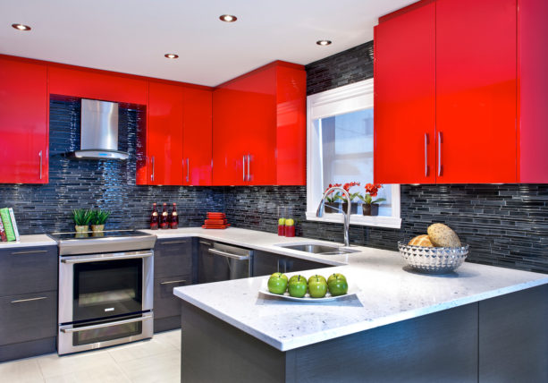 a unique combination between bright red wall cabinets and black matchstick tile backsplash