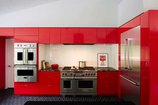red contemporary kitchen with black subway tile flooring