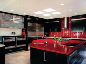 the combination between black cabinets and island with glossy red countertops and tiled backsplash