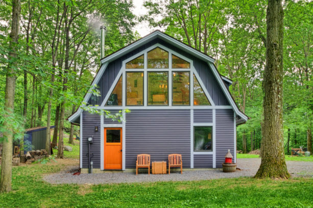 a barn-style house with grey siding, white trim, and orange front door