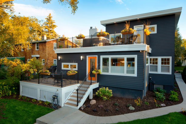 a contemporary exterior with dark-charcoal painted siding, white trim, and bright orange door
