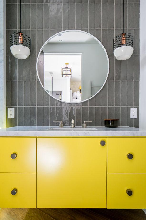 a floating flat-panel vanity cabinet paired with grey vertical glass subway tile for a color shot