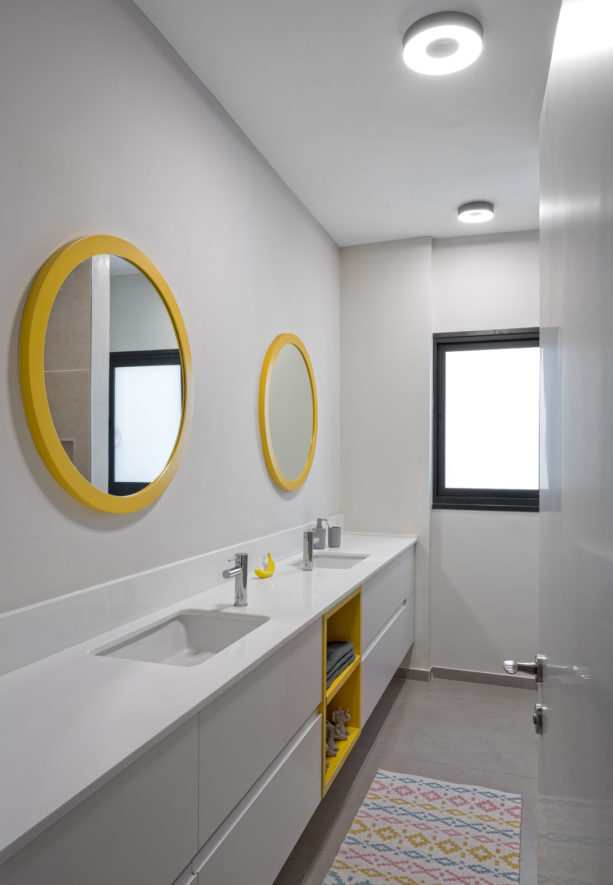 a grey contemporary bathroom with two round yellow wall mirrors