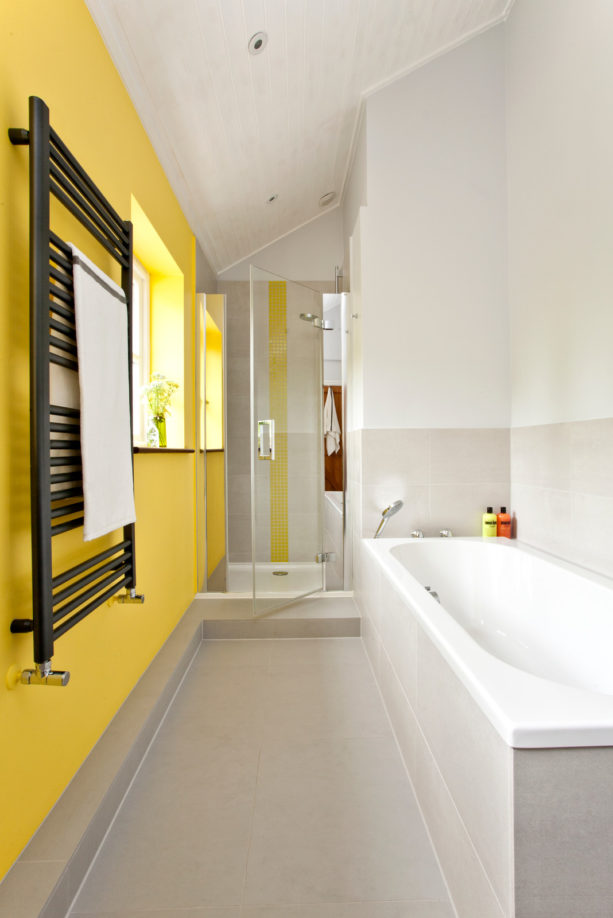 a grey contemporary bathroom with yellow accent wall