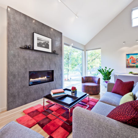a grey living room with multi-tone red rug under the black coffee table