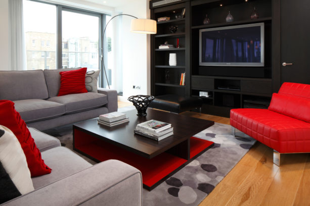 a modern living room with red, black, and grey color scheme