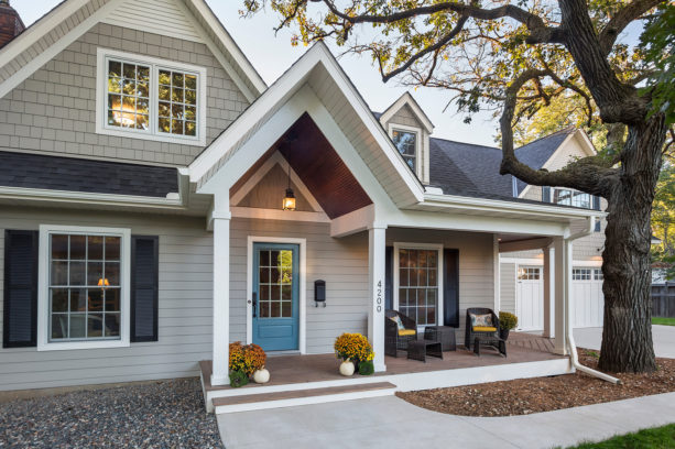 a traditional grey exterior with white trim and blue French door