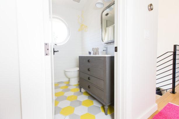 a transitional bathroom with fun multicolor hexagonal tile floor