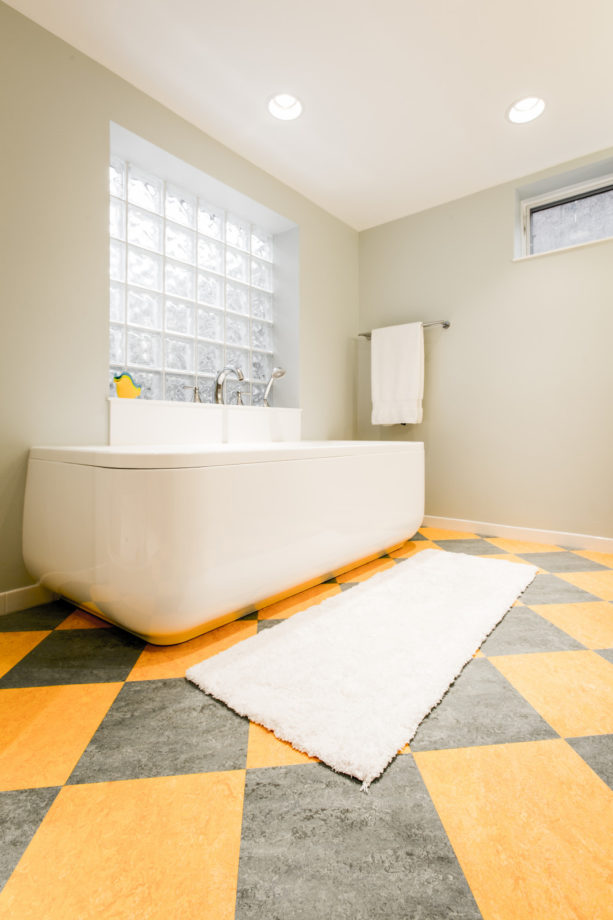 a unique grey and yellow floor in a transitional bathroom