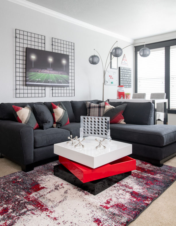 bold living room interior with charcoal grey sectional and red detailing