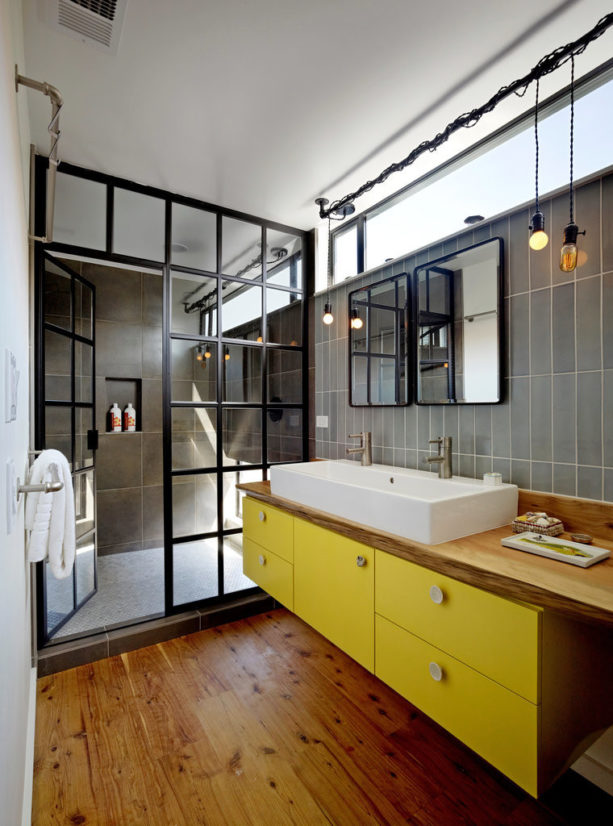 the combination of grey, yellow, black, and wood colors in an industrial bathroom