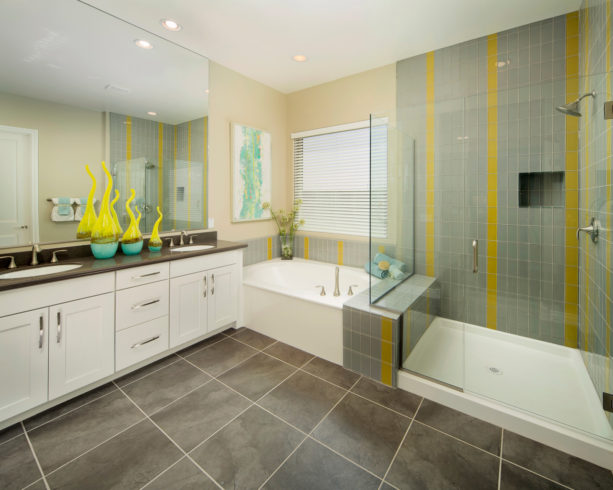 the use of grey and yellow glass tiles for a shower room's walls