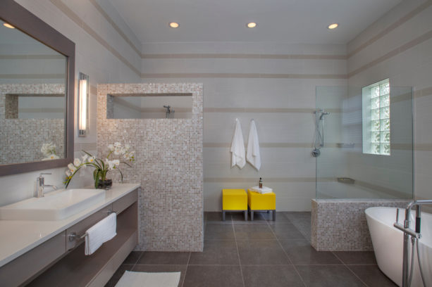 two catchy yellow stools in a grey contemporary bathroom
