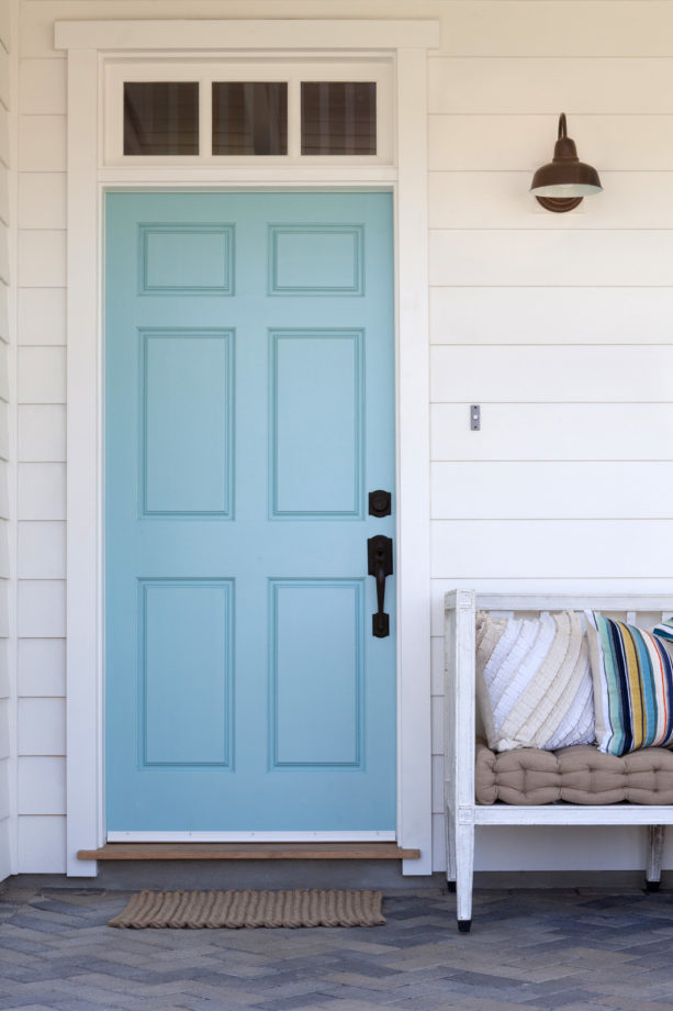 a light blue farmhouse front door with small transom and simple butted trim